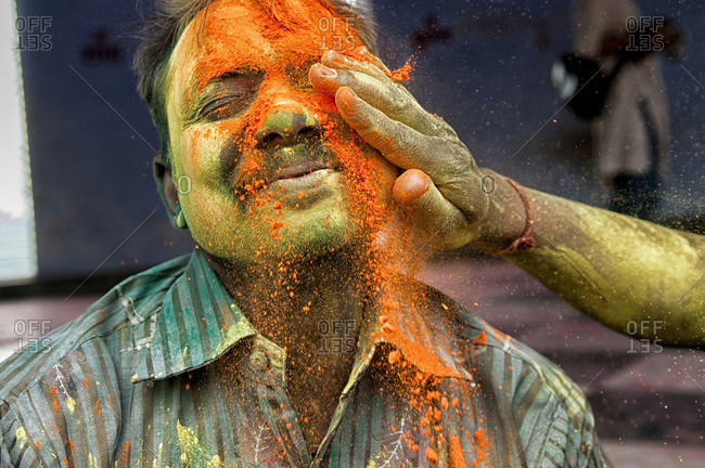 Nandgaon, Uttar Pradesh, India - March 10, 2014: A man gets colored powder slapped in his face during Holi Festival