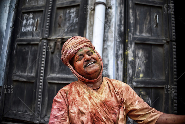 Nandgaon, Uttar Pradesh, India - March 10, 2014: Portrait of laughing man covered in colored powder during Holi Festival