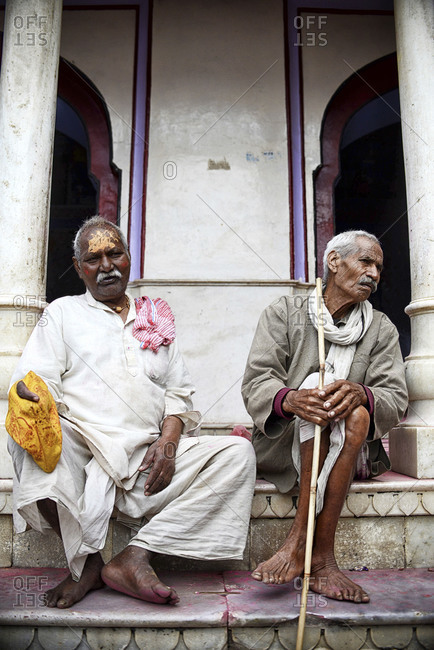 Nandgaon, Uttar Pradesh, India - March 10, 2014: Portrait of two men sitting on temple steps during Holi festival