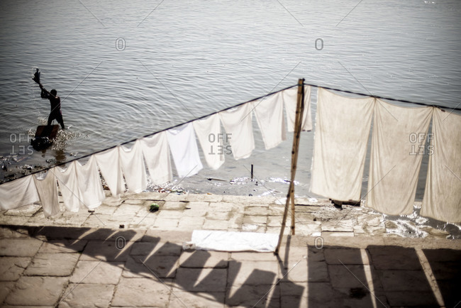 Man washing clothes in the Ganges river in Varanasi, India
