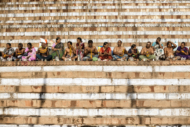 Varanasi, India - March 21, 2014: People sitting side-by-side on a ghat