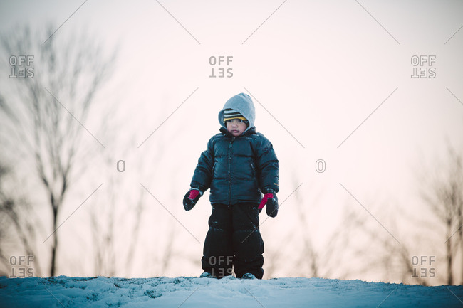 Boy standing on snowy hilltop