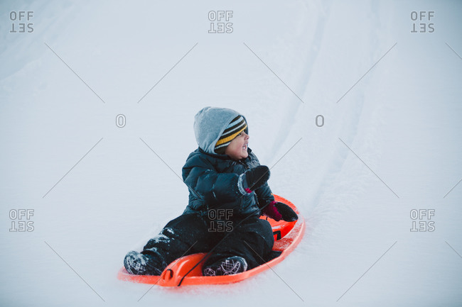 Boy bundled up on sled