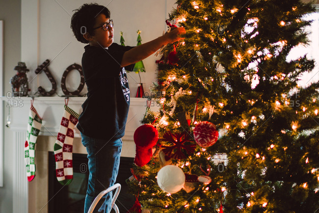 Boy on step ladder decorating Christmas tree