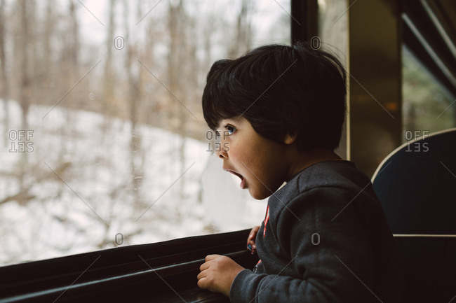Boy looking out window in winter