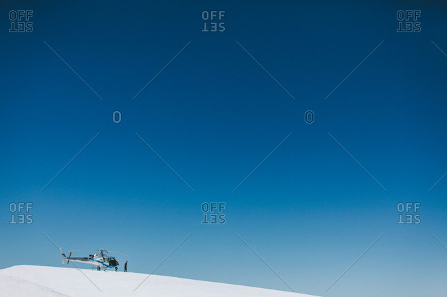 Person standing next to helicopter on snowy summit