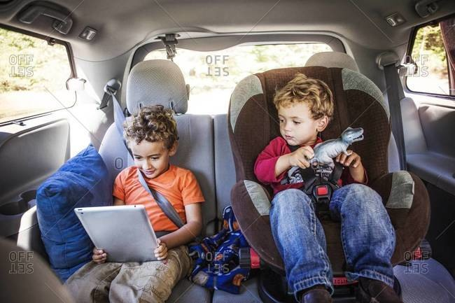Two brothers watch a tablet in the backseat of a van