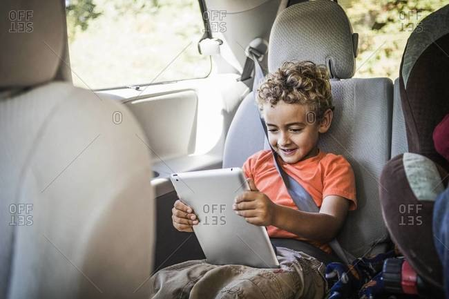 A boy watches a tablet in the backseat of a van
