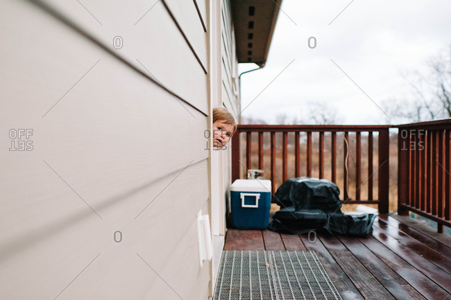 Young girl peeking out of a house