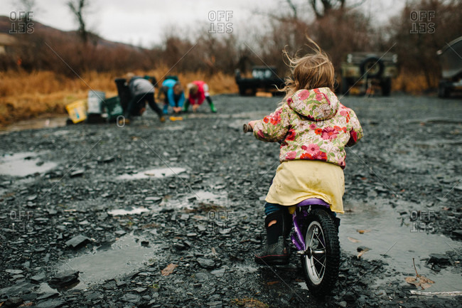 Young girl riding a bicycle on a wet road