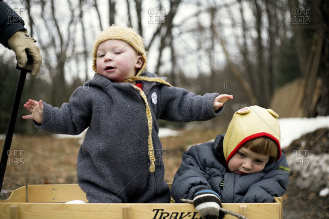Two children sit in a wagon