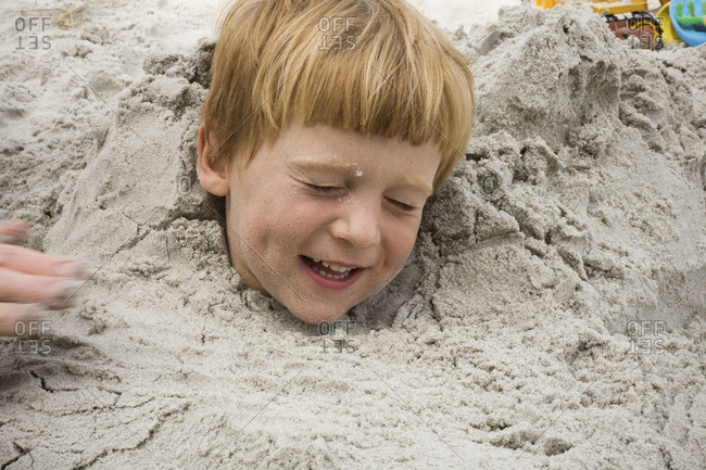 A boy buried in the sand