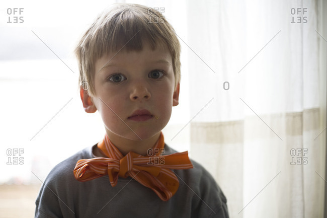 A little boy with a ribbon tied around his neck