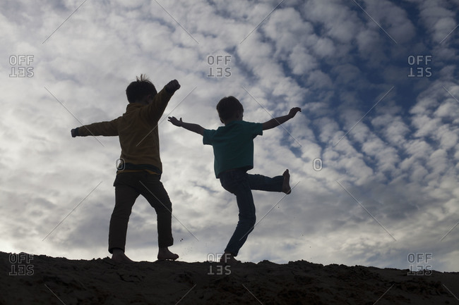 Two boys walk on the top of a sand dune