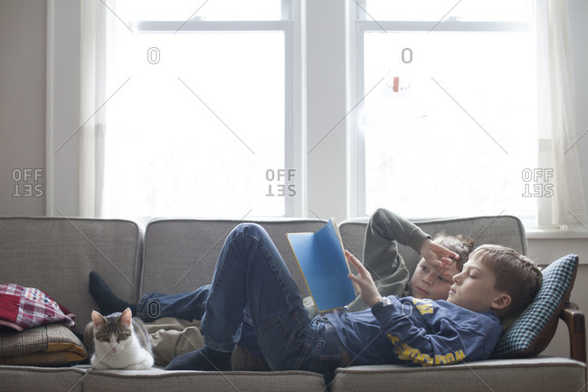 Two boys read a book together