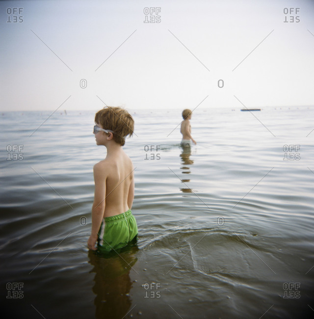 Two boys wade into the water