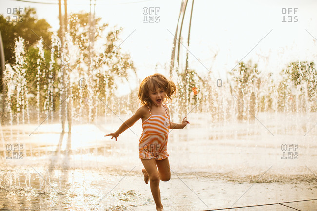 Girl running in fountains in park