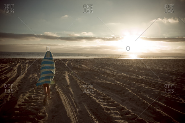 Child walking on a beach at sunset