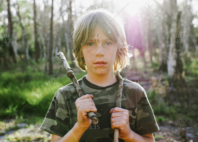 Portrait of boy holding sticks in a forest
