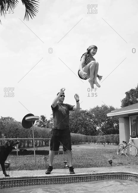 Dad tossing daughter into a pool