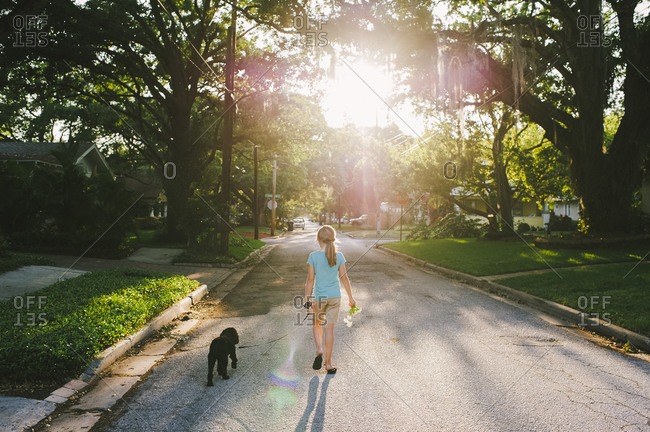 Back view of girl walking her dog