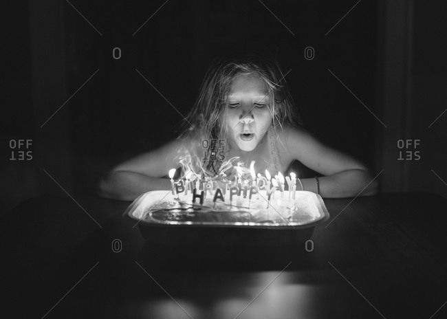 Girl blowing out the candles on her birthday cake