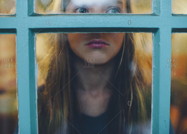 Young girl staring out of a window