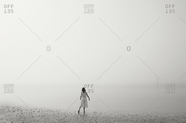 Young girl standing on a misty beach