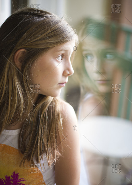Portrait of a girl staring out of a window