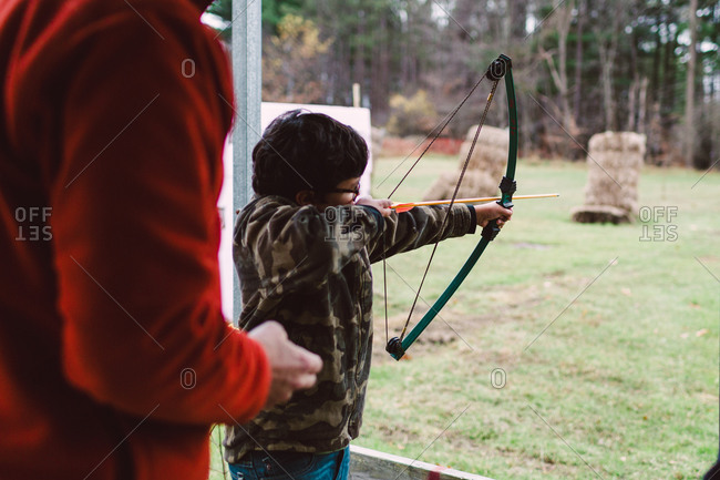 Boy practicing archery while man oversees