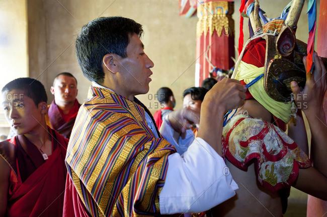 Gangtey Dzong, Phobjikha Valley, Bhutan - October 10, 2011: Man helps a dancer with his mask at a festival