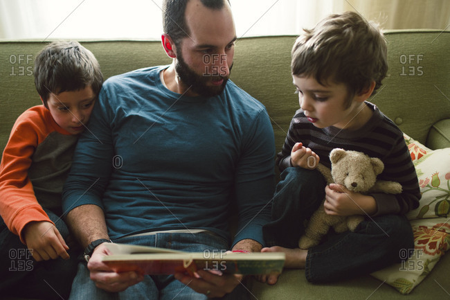 Man reading to two boys on couch