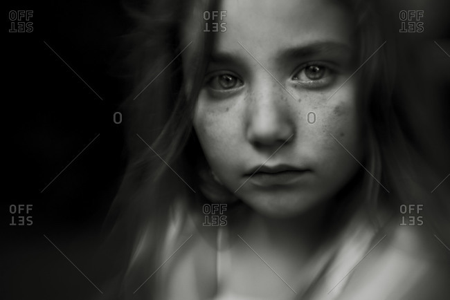 Portrait of sad girl with dark background
