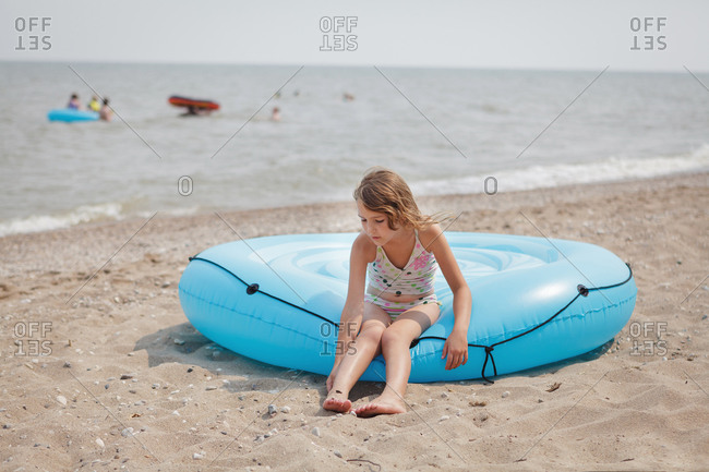 Girl sitting on inflatable raft on sand