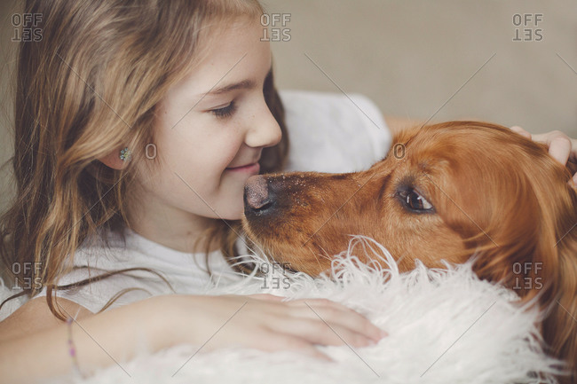 Girl and dog cuddling together