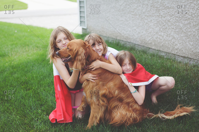 Girls hugging their dog outside