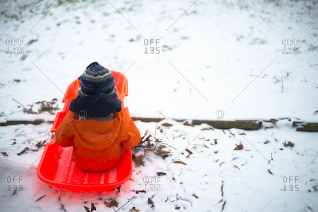 Boy in sled in yard