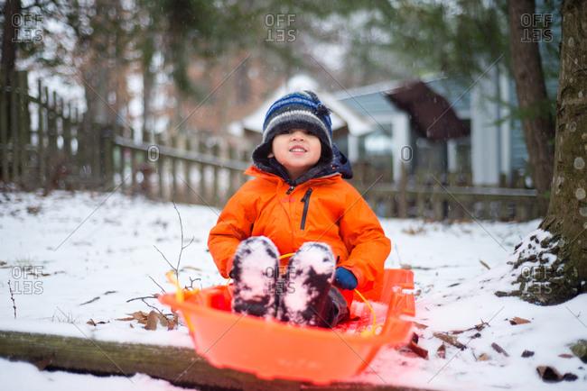 Boy sitting on sled in yard