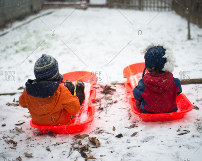 Two boys in sleds in yard