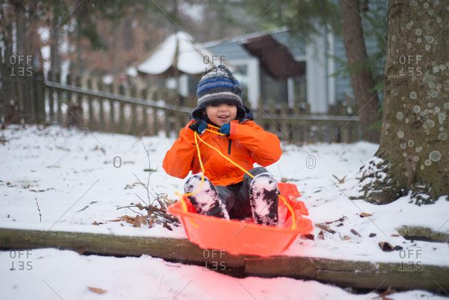 Boy pretending to sled in yard