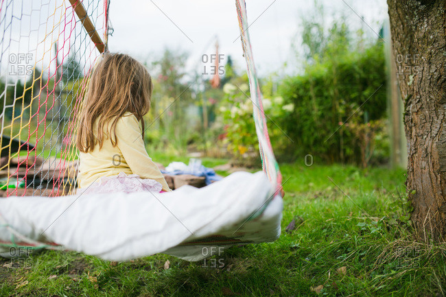 Solitary girl in hammock swing outside