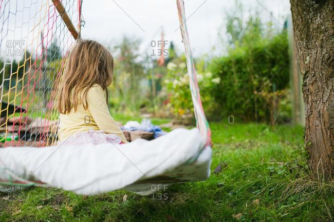 Solitary girl in hammock swing outside