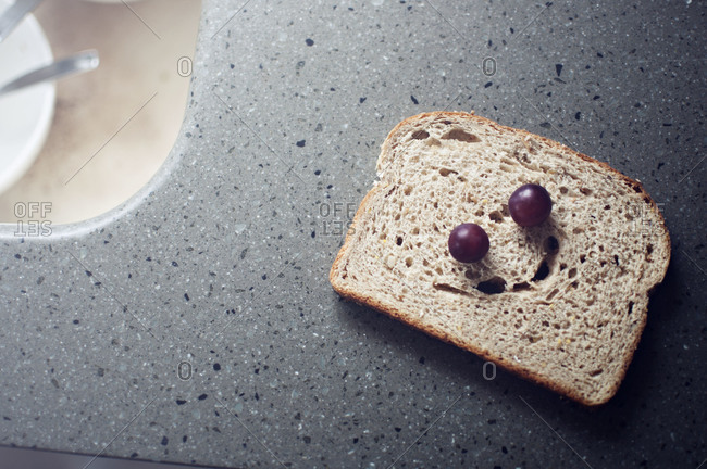Bread and grapes making smiley face