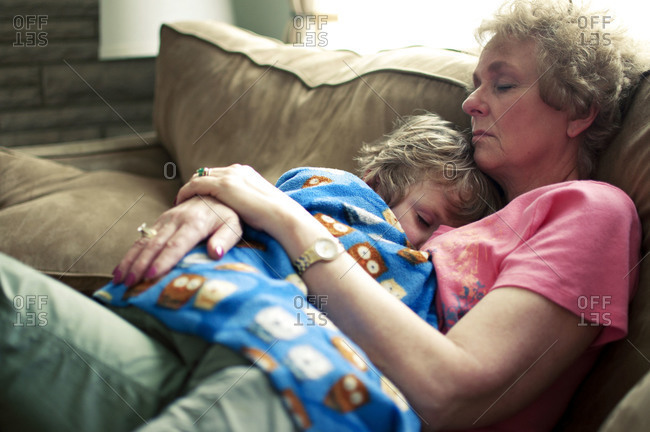 Boy sleeping in grandmother's arms