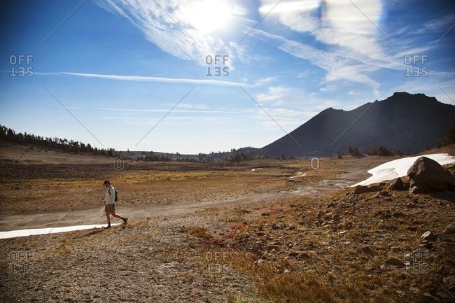 A man hikes across a field