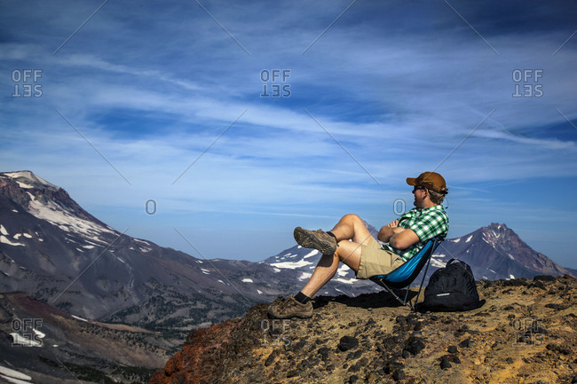 A man relaxes on a mountain top
