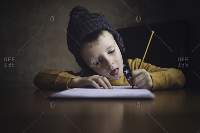Boy writing intently with pencil