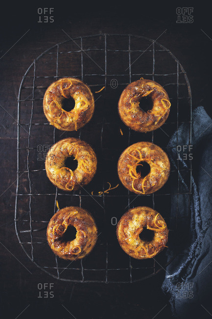 Orange and poppy seed bundt cakes on a cooling rack