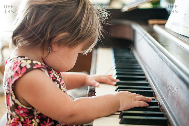 A baby girl plays the piano