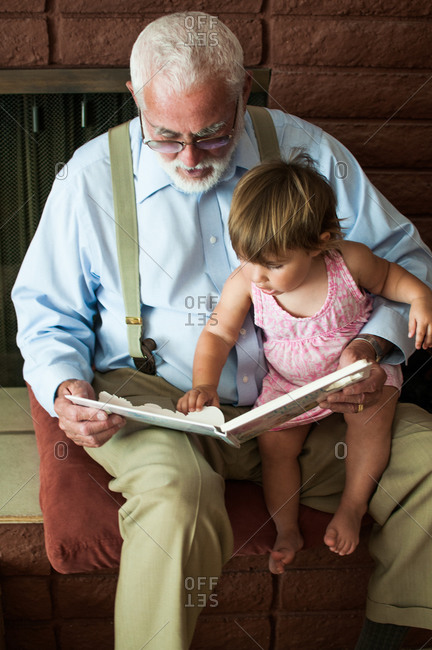 A grandfather reading to his granddaughter